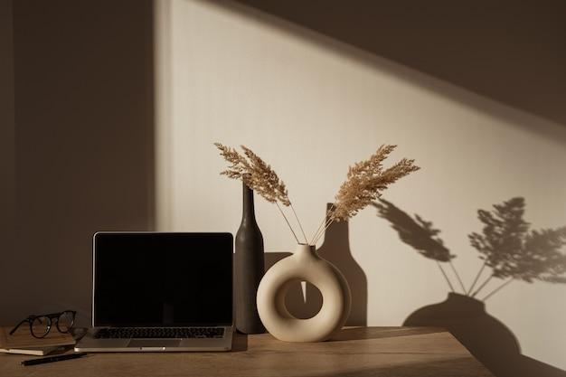 Computer portatile con schermo vuoto sul tavolo con bouquet di erba di pampa in ombre di luce solare sul muro