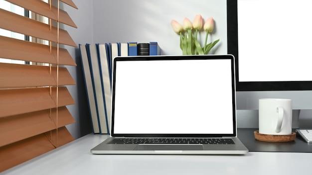 Computer portatile con schermo vuoto sul tavolo bianco in un moderno ufficio a casa.