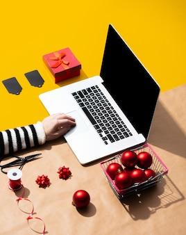Computer portatile con mano femminile e regali di natale, oggetti per il confezionamento