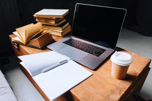 Computer portatile sul tavolo di legno con libri, taccuino e tazza di caffè al mattino.