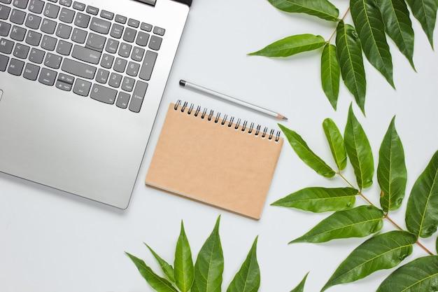 Laptop, taccuino artigianale su sfondo bianco con foglie verdi. concetto di unità con la natura. eco ancora in vita. vista dall'alto