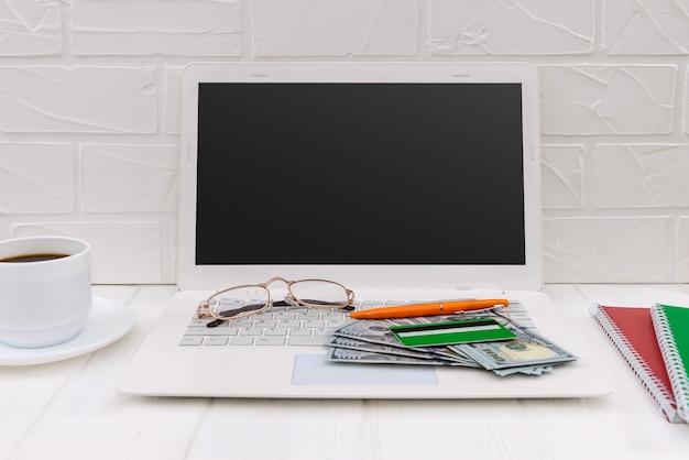 Laptop, carta di credito, dollari e tazza di caffè