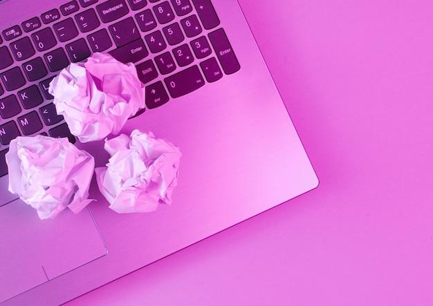 Computer portatile, palle di carta sgualcite da vicino. luce rosa olografica