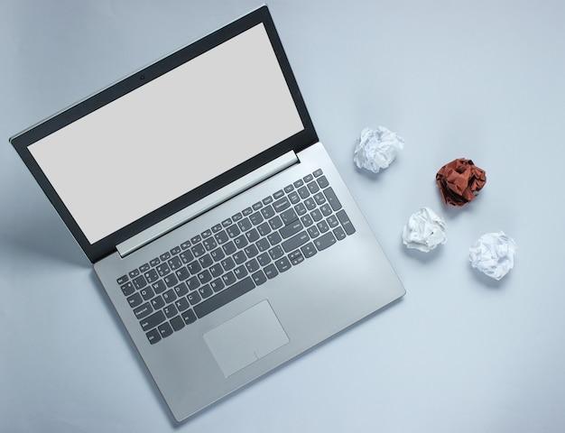 Computer portatile e palle di carta sgualcite sulla tavola grigia. concetto di business minimalista. vista dall'alto