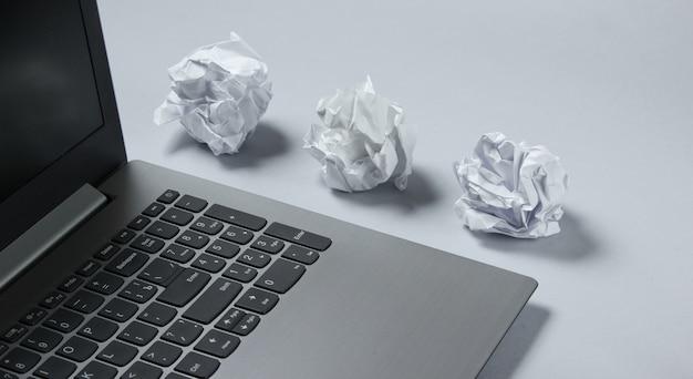 Computer portatile e palle di carta sgualcite sulla tavola grigia. concetto di business minimalista.
