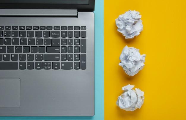 Computer portatile e palle di carta sgualcite sulla tavola blu gialla. concetto di business minimalista. vista dall'alto