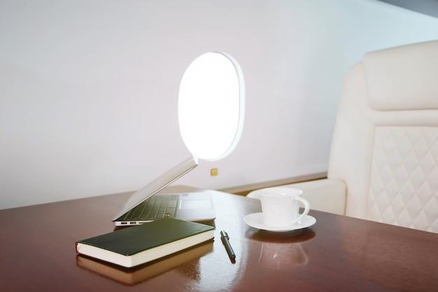 Computer portatile, diario e tazza di caffè sul tavolo degli interni di lusso in jet privato