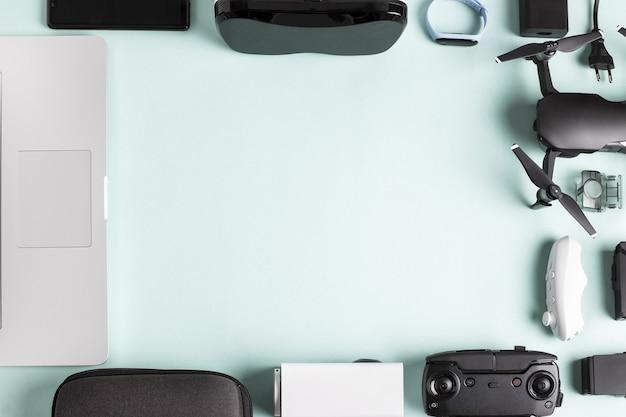 Laptop e drone vicino a vari accessori, piegati come una cornice sul blu