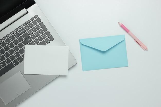 Laptop e busta con lettera su sfondo bianco. san valentino. vista dall'alto