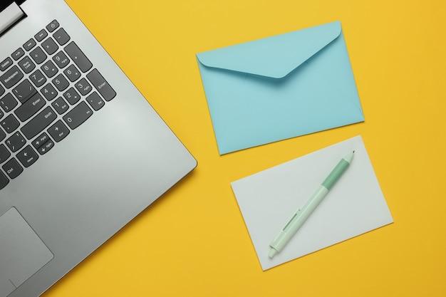Laptop e busta con lettera su sfondo giallo. san valentino. vista dall'alto
