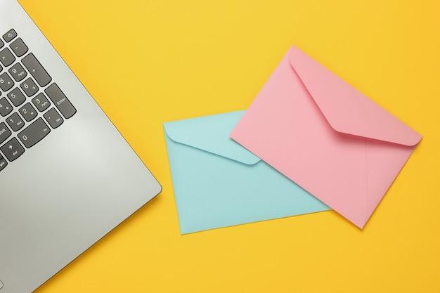 Laptop e buste su sfondo giallo. san valentino. vista dall'alto