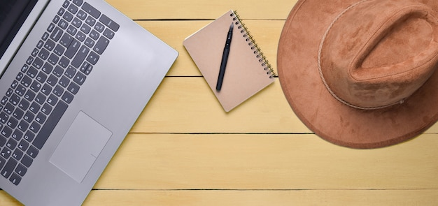 Computer portatile, cappello di feltro, taccuino e penna su una tavola di legno gialla