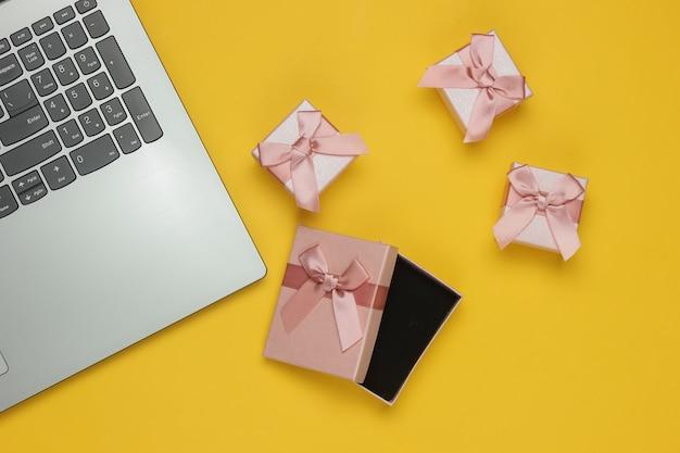 Scatole regalo e laptop con fiocco su sfondo giallo. composizione per natale, compleanno o matrimonio. vista dall'alto