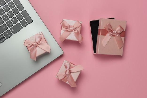 Scatole regalo e laptop con fiocchi su sfondo rosa pastello. composizione per natale, compleanno o matrimonio. vista dall'alto