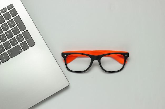 Laptop e occhiali senza lenti su sfondo bianco. concetto di freelance. lay piatto. vista dall'alto