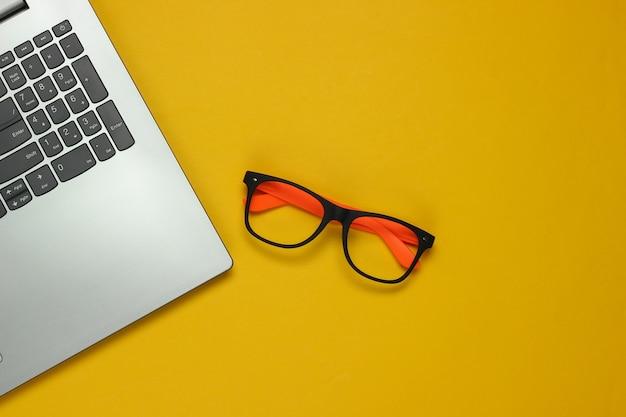 Laptop e occhiali senza lenti su sfondo giallo. concetto di freelance. lay piatto. vista dall'alto