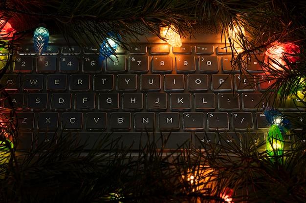Tastiera portatile circondata dalle luci di una ghirlanda di natale. decorazioni natalizie al computer. tecnologia e concetto di natale