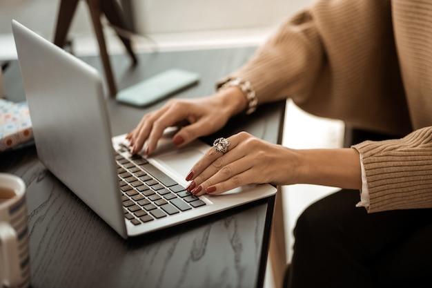 Tastiera portatile. donna ordinata in maglione beige con manicure rossa e anello di rarità al dito
