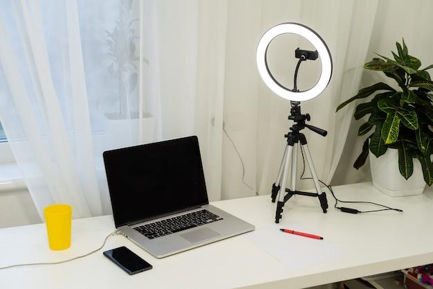 Laptop, lampada e treppiede sul tavolo per l'intervista online