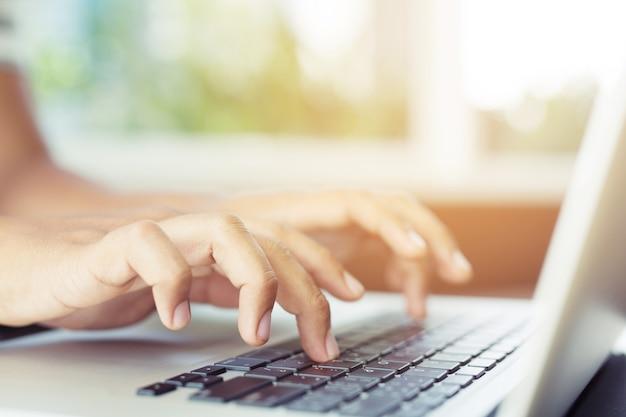Il computer portatile. stile di vita donna vicino la tastiera della mano sedersi sul divano utilizzando un computer notebook per lavorare da casa e cercare informazioni sul social network online.