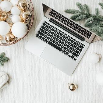 Computer portatile sdraiato sul tavolo di legno decorato con rami di albero di natale, cesto festivo di palline bianche e oro