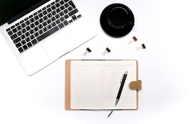 Notebook portatile tazza di caffè e fiore su sfondo bianco