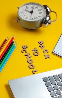 Computer portatile e taccuino con matite colorate vicino a un orologio