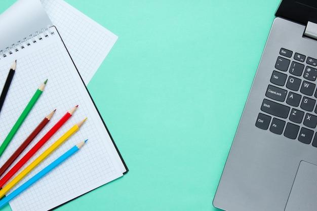 Laptop e taccuino con matite colorate