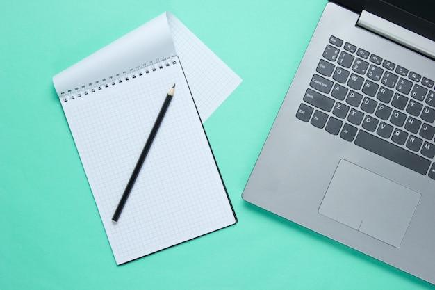 Computer portatile e taccuino con la matita isolata sull'azzurro
