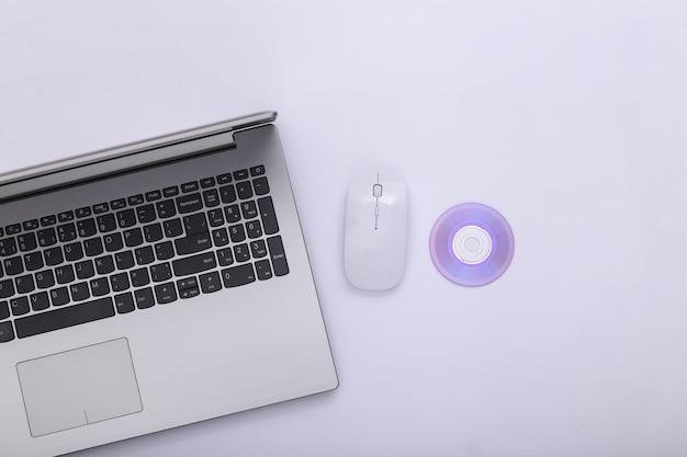 Computer portatile, mouse del pc con il cd su fondo bianco. vista dall'alto
