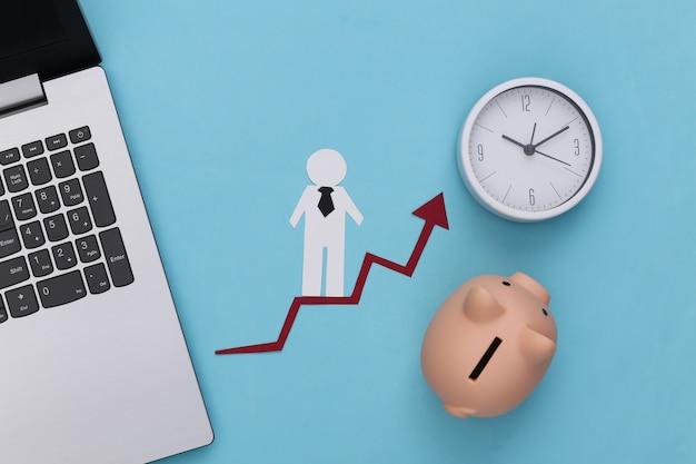 Computer portatile, salvadanaio, orologio e uomo di carta sulla freccia di crescita.