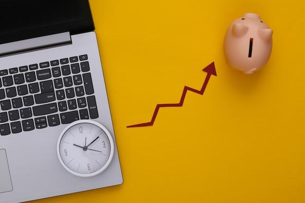 Computer portatile, salvadanaio con orologio e freccia di crescita rossa su giallo. grafico a freccia che sale