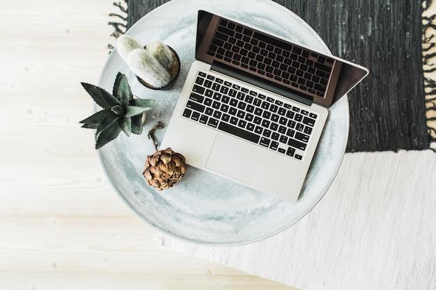 Computer portatile, fiore di protea e succulente sul tavolo. disposizione piatta, vista dall'alto