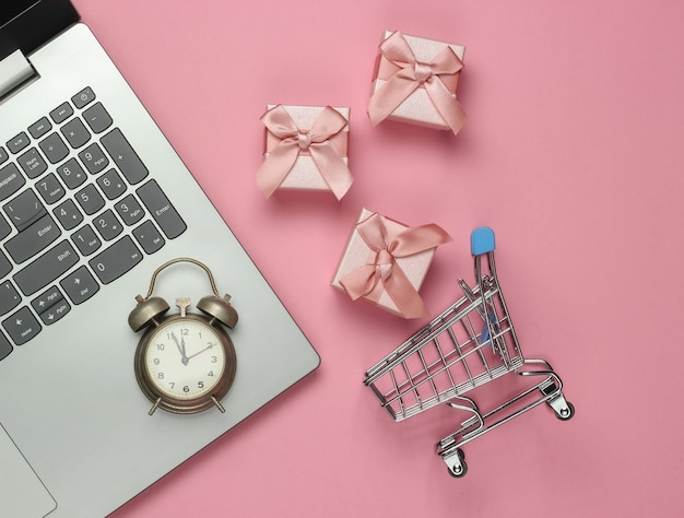 Computer portatile, sveglia retrò, carrello della spesa, scatole regalo con fiocco su sfondo rosa pastello. 11:55. anno nuovo, concetto di natale. shopping per le vacanze. vista dall'alto