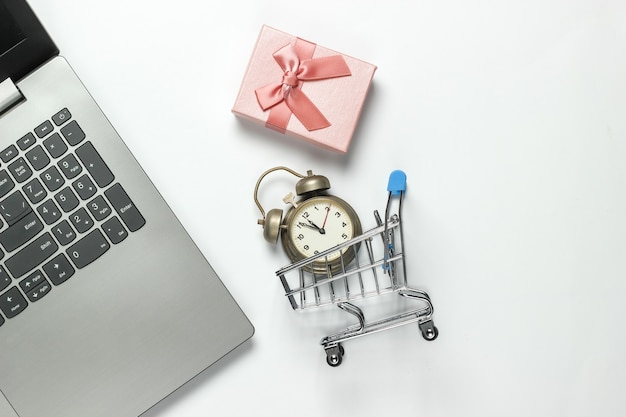 Computer portatile, sveglia retrò, carrello della spesa, scatole regalo con fiocco su sfondo bianco. 11:55. anno nuovo, concetto di natale. shopping in linea di vacanze. vista dall'alto