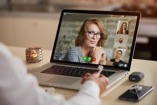 Una vista dello schermo del laptop dell'applicazione di telecomunicazioni durante una riunione in linea sopra la spalla di un uomo.
