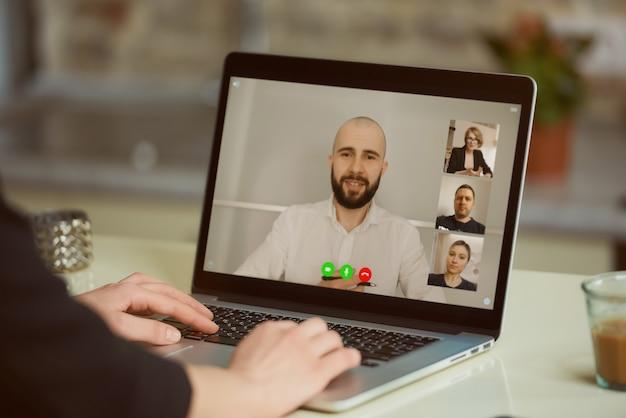 Una vista dello schermo del laptop sopra la spalla di una donna. una ragazza sta ascoltando una dichiarazione del suo collega durante un briefing online