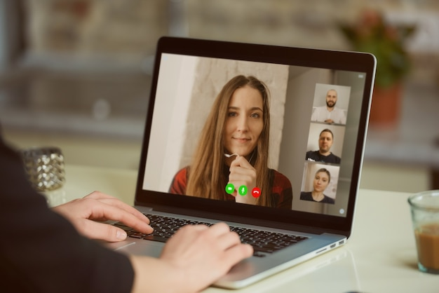 Una vista dello schermo del laptop sopra la spalla di una donna. una ragazza sta ascoltando una dichiarazione della sua collega durante un briefing online