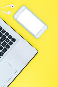 Computer portatile e smartphone con uno schermo bianco e le cuffie sui precedenti gialli.