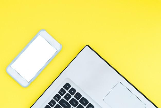 Un laptop e uno smartphone con uno schermo bianco su uno sfondo giallo.