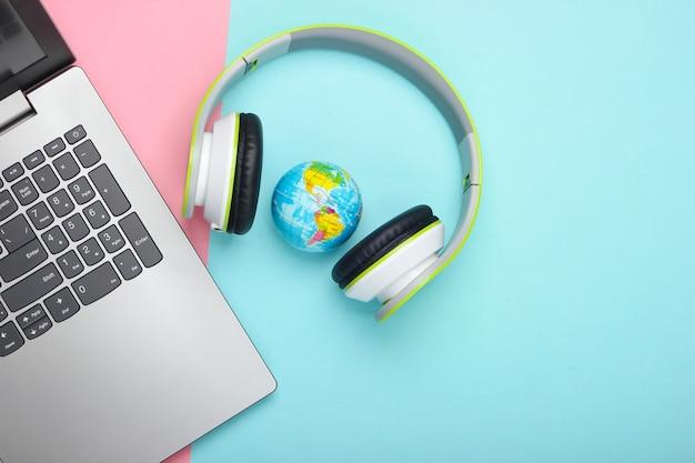 Computer portatile, cuffie stereo e globo sulla superficie rosa e blu