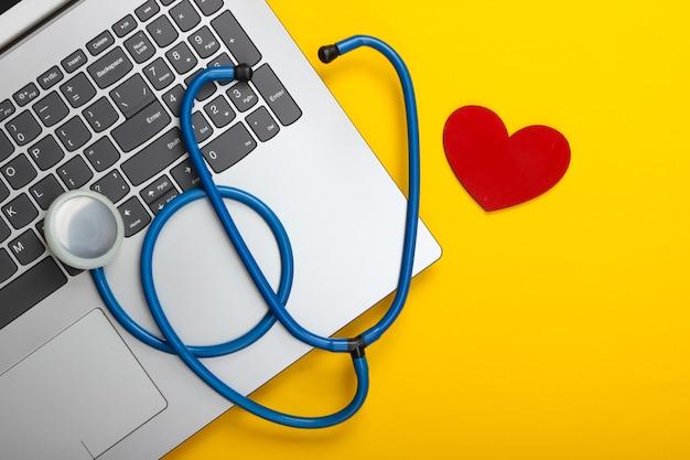 Computer portatile e stetoscopio con cuore su colore giallo