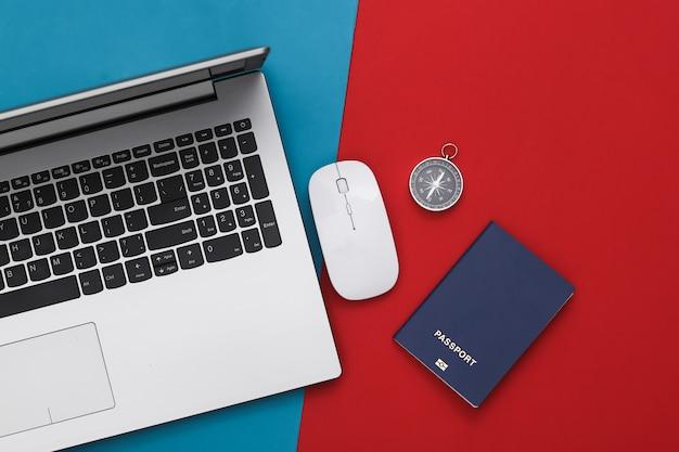 Laptop e accessori da viaggio su rosso-blu. pianificazione del concetto di viaggio