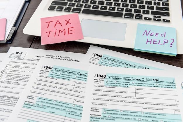 Laptop e modulo fiscale statunitense in ufficio, contabilità aziendale. documento finanziario