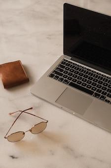 Computer portatile, portafoglio, occhiali da sole sul tavolo di marmo. area di lavoro della scrivania dell'ufficio domestico