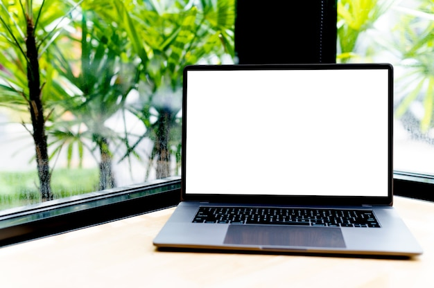 Computer portatile con schermo vuoto sulla scrivania, in ufficio, spazio vuoto. concetto di lavorare con il laptop e lavorare con la comunicazione online online