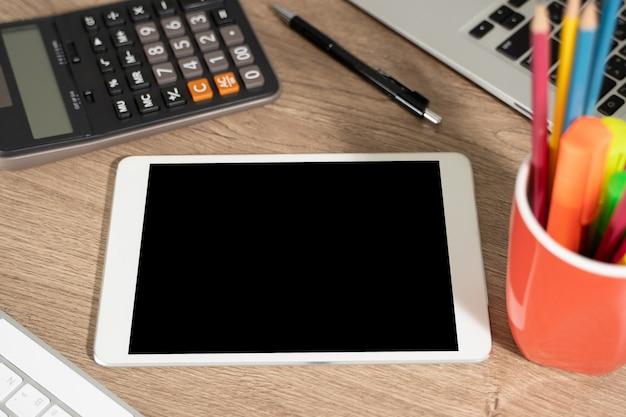 Computer portatile con schermo bianco sul tavolo. schermo dello spazio della copia in bianco del fondo dell'area di lavoro