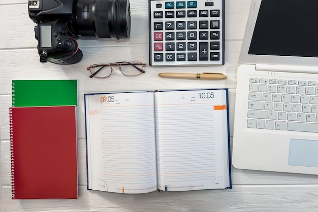 Computer portatile con calcolatrice e fotocamera digitale al tavolo