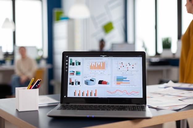 Computer portatile con grafici finanziari dell'azienda sulla scrivania dell'ufficio. area di lavoro nel centro affari con dipendenti multietnici, inquadratura di una stanza con mobili moderni e parete blu.