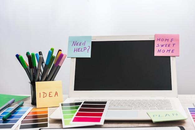 Computer portatile con campioni di colore di design sul posto di lavoro.